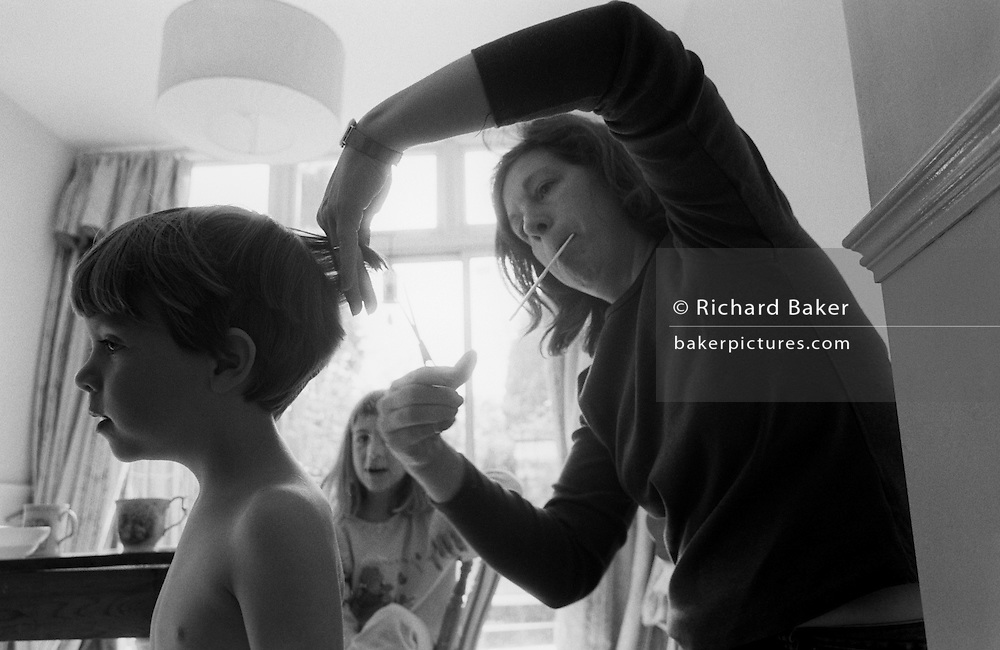 "A young three year-old boy has his hair cut by his mother in the family South London home. Lifting his hair with her fingers, the mum snips with a pair of scissors. While lifting her left elbow to gain the right angle of her cutting, we see her holding a comb in her mouth. The boy's elder sister looks on offering unhelpful comments which will eventually lead to an exchange of unkind words between the siblings while their mother concentrates hard on not making a mess of the kid's haircut. From a personal documentary project entitled ""Next of Kin"" about the photographer's two children's early years spent in parallel universes. Model released."