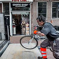 """Nederland, Amsterdam, 24 juni 2016.<br /> Elke maand organiseerde het Fietsdepot voor professionele opkopers een veiling van de fietsen die niet binnen zes weken zijn opgehaald door hun eigenaar. Maandagochtend vindt voor de laatste keer een fietsveiling plaats. Voor die speciale gelegenheid neemt wethouder Pieter Litjens (Verkeer) de veilinghamer ter hand.<br /> Vanaf 1 juli is het Haarlemse bedrijf TradeFRM verantwoordelijk voor de verkoop van niet-opgehaalde fietsen aan handelaren en aan socialewerkprojecten. """"Ook het niet verkoopbare materiaal zal door TradeFRM op de meest duurzame manier worden gerecycled en hergebruikt,"""" aldus de gemeente.<br /> Alle door de gemeente weggeknipte fietsen komen terecht op het terrein van het Fietsdepot in het Westelijk Havengebied. Amsterdammers kunnen daar terecht om hun weggeknipte fiets weer op te halen. Dat kost sinds 1 januari dit jaar 22,50 euro. Daarvoor was dat 15 euro. Thuis laten bezorgen kan ook, voor 50 euro. Iets minder dan de helft van de fietsen worden door de eigenaar opgehaald.<br /> Op de foto: Fietsen die te lang langs de grachten blijven staan worden door de Gemeente weggesleept.<br /> <br /> <br /> Foto: Jean-Pierre Jans"""