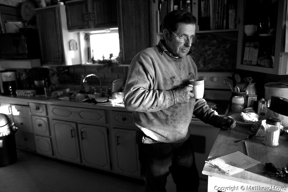 "AUBURN, NEW YORK - MARCH 06: Joe Tidd drinks a cup of coffee in the kitchen of his farm house in Auburn, NY. Joe runs a small dairy farm in upstate New York. They have been hit hard by the recent drop in milk prices. They recently had to get rid of their health insurance because it had gotten too expensive. ""I would have killed myself if it had not been for my wife and kids,"" explained Joe with steely seriousness while talking about the economic hardships they have faced. ""That's how bad it was."""