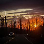 A lone car drives along the road during sunset inside Yosemite National Park on Sunday, September 22, 2019 in Yosemite, California. (Alex Menendez via AP)