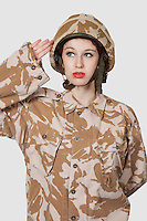 Young woman in military uniform saluting against gray background