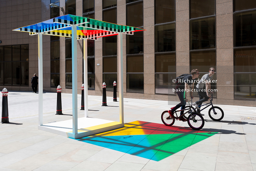 """Cyclists pedal past the artwork entitled """"4 Colours at 3 Meter High"""" by Daniel Buren leaves multi-coloured patterns from strong sunlight  on the pavement at One Creechurch Place, on 17th Juy 2017, in the City of London, England."""