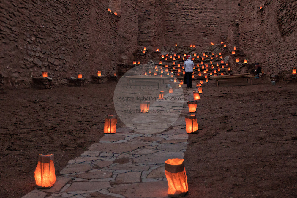 A woman views the ruins of the San José de los Jémez Mission part of the Jemez Historic Site illuminated by hundreds of small paper lanterns known as luminaria to celebrate the holiday season December 12, 2015 in Jemez Springs, New Mexico. The site is in the Jémez Indian pueblo and contains an early 17th-century mission complex.
