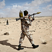 A rebel fighter makes his way towards the town of Ajdabiya, 100 miles south of Benghazi, Libya during clashes with government troops. March 2011.
