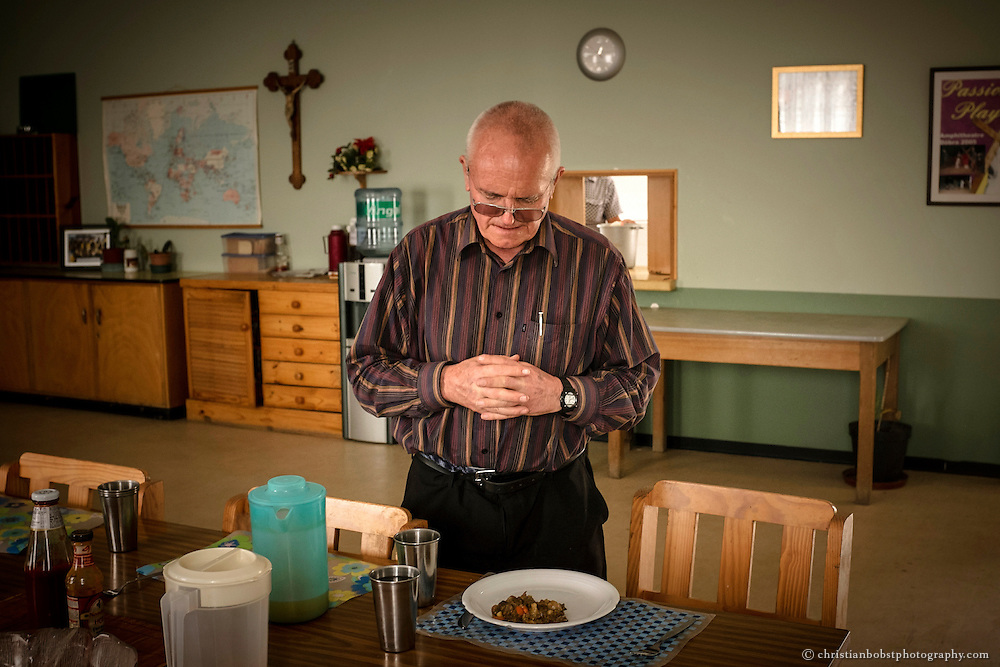 (2013)  Father Hermann prays before eating dinner at the mess hall of the church where he lives in a small apartment.