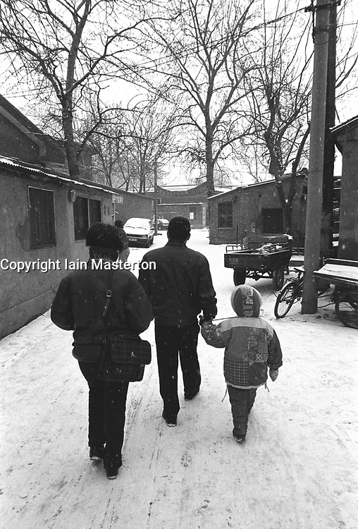 Family walking in snow in a hutong in Beijing