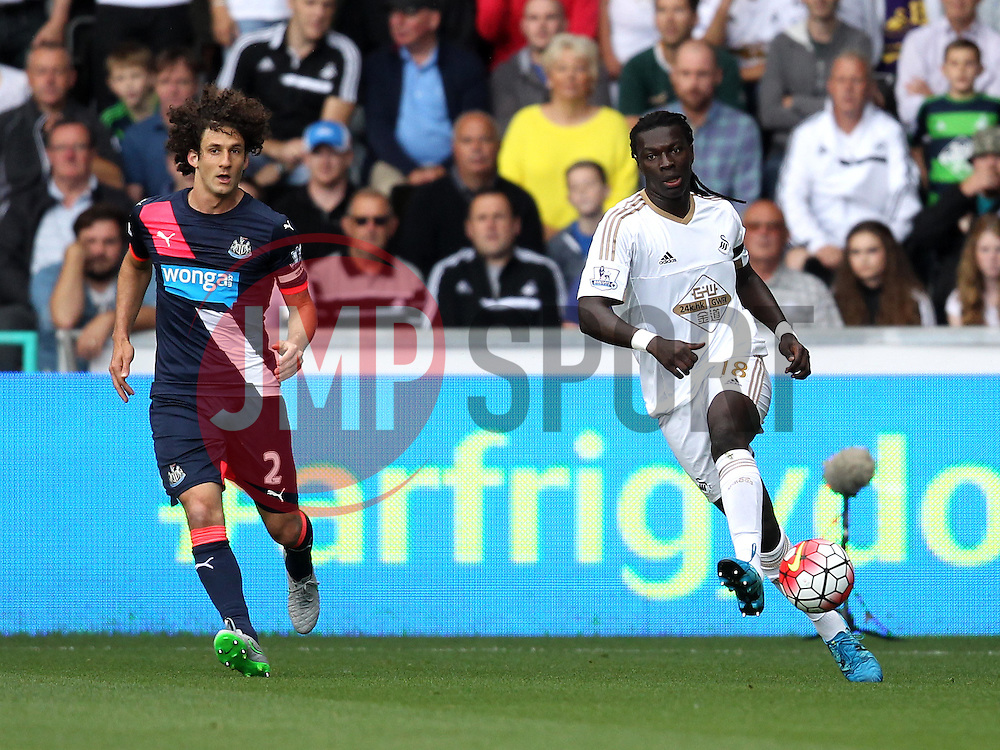 Bafetibis Gomis of Swansea City passes the ball under pressure from Fabricio Coloccini of Newcastle United - Mandatory byline: Robbie Stephenson/JMP - 07966386802 - 15/08/2015 - FOOTBALL - Liberty Stadium -Swansea,England - Swansea City v Newcastle United - Barclays Premier League