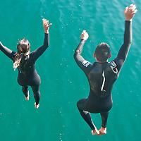 Reina Alvarez, 31, and Sandy Gallardo, 21, jump into the ocean from the Santa Monica Pier while participating in a Santa Monica Harbor Patrol rescue drill on Friday, December 9, 2011.