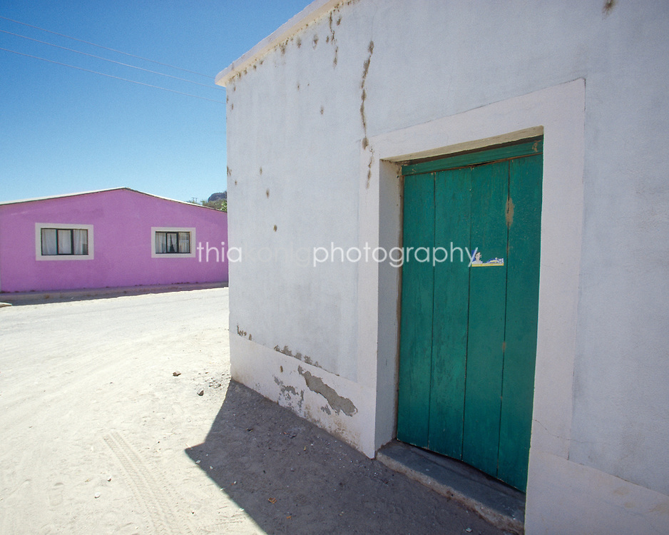 Desert buildings in a Mexican village, Baja, Mexico. White wall, green door, with pink building in the background.
