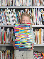 Girl holding stack of books in library portrait