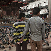 two man standing stand in front of a temple which is partially damaged in Kathmandu