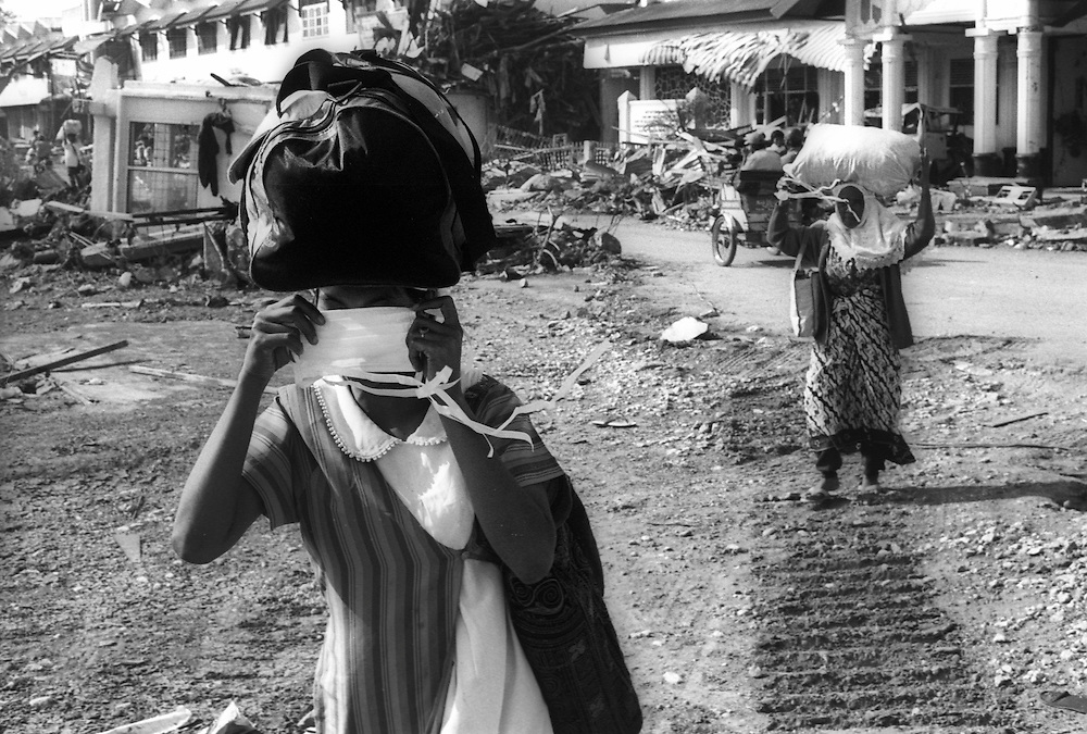 Women leaving cover their mouths to help reduce the smell of death from the many exposed bodies still in the Tsunami devstated city of Banda Aceh. January 2005