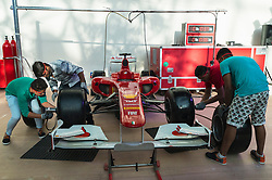 Visitors changing wheels of Ferrari Formula 1 car at pit stop challenge at Ferrari World in Abu Dhabi United Arab Emirates