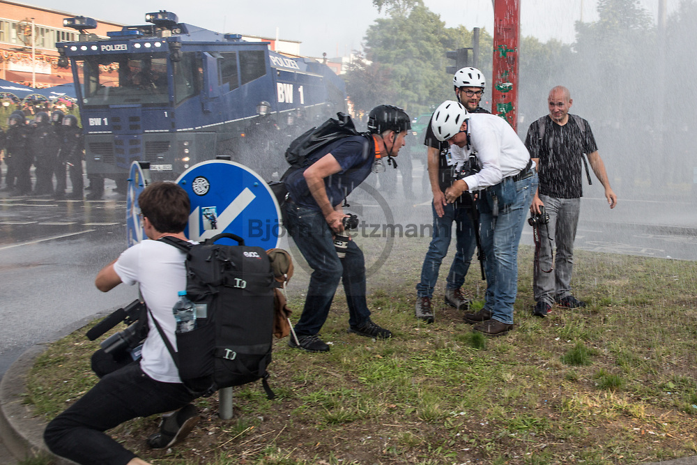 Hamburg, Germany - 07.07.2017<br /> <br /> Auf dem Pferdemarkt stehen Journalisten im Wasserwerfer-Regen. Dieser zielte am Rande der G20-Ausschreitungen unerwartet auch auf eine Verkehrsinsel auf der sich ausschlie&szlig;lich Pressevertreter aufhielten.<br /> <br /> Photo: Bjoern Kietzmann