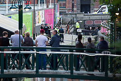 "© Licensed to London News Pictures . Manchester , UK . FILE PICTURE DATED  06/10/2013 of onlookers watching as police drain a lock in Manchester City Centre , to recover a body . Police pulled a body from The Bridgewater Canal in Manchester , adjacent to the City's "" Gay Village "" on Canal Street . Greater Manchester Police have issued a statement after suggestions that a number of deaths in and around Manchester's canals may be linked to a serial killer , named in local folklore as "" The Pusher "" . The statement said "" Absolutely no evidence whatsoever of foul play has been established "" . Photo credit : Joel Goodman/LNP"
