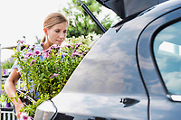 Portrait of mature female gardener putting flowers on car trunk for delivery