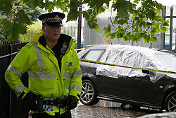 © licensed to London News Pictures. Salford, UK 18/7/2011. An abandoned Saab car, used in the armed hijack of two prisoners from a police van, in Salford, being watched over by police.. Please see special instructions for usage rates. Photo credit should read Joel Goodman/LNP