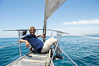 Full-length of happy man sitting on bow of yacht