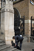 A man stoops to tie his shoelace at Liverpool Street Station in the City of London, the capital's financial district aka the Square Mile, on 15th May 2018, in London, UK.