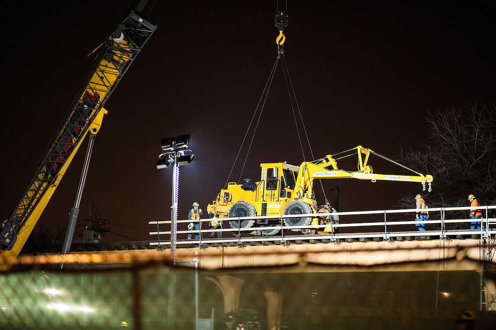 """A tractor is lowered onto the CTA Blue Line O'Hare branch tracks as the """"Your New Blue"""" improvement project begins on Friday, March 21, 2014."""