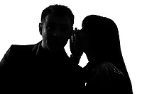 one caucasian couple man and woman  whispering at ear in studio silhouette isolated on white background