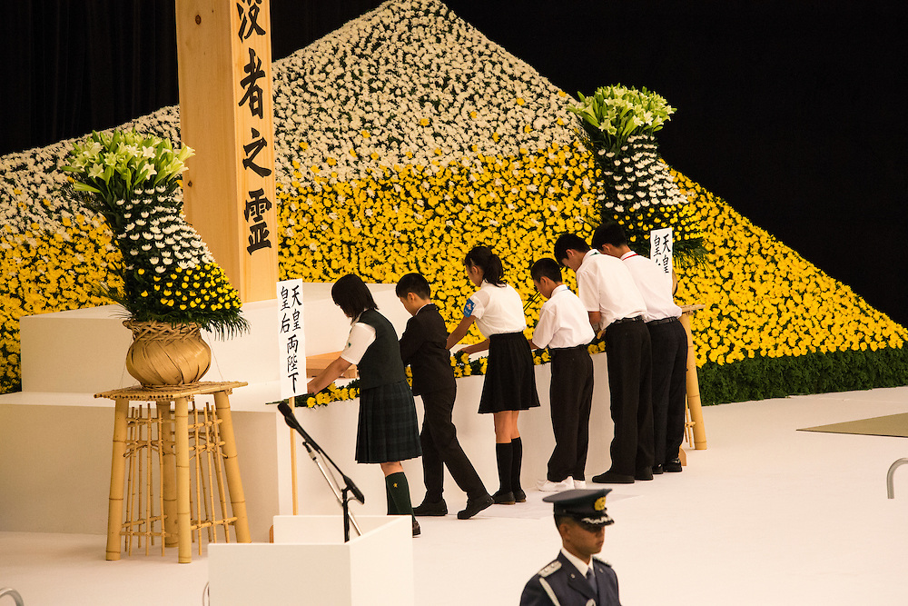TOKYO, JAPAN - AUGUST 15 : People offer flowers to pay respects during the memorial service at the Nippon Budokan on the 71st anniversary of the Japan's war surrender on August 15, 2016 in Tokyo, Japan. (Photo by Richard Atrero de Guzman/NURPhoto)