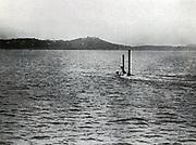Submarine running submerged, with periscope exposed.