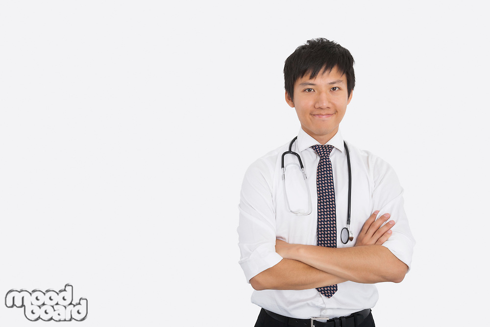 Portrait of Asian male doctor with arms crossed over white background