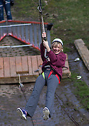 Michele Benjamin, a mother visiting for Mom's weekend, laughs as her ride on the Outdoor Pursuits zipline at the Challenge Course at the Ridges comes to a close on Saturday afternoon, April 5, 2014. Photo by Katelyn Vancouver / Ohio University