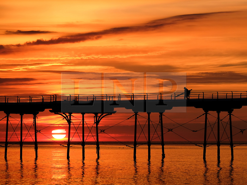 © Licensed to London News Pictures. <br /> 28/08/2017<br /> SALTBURN-BY-THE-SEA, UK.  <br /> A fisherman walks to the end of the pier at sunrise in Saltburn-by-the-Sea on Bank Holiday Monday.<br />   <br /> Photo credit: Ian Forsyth/LNP