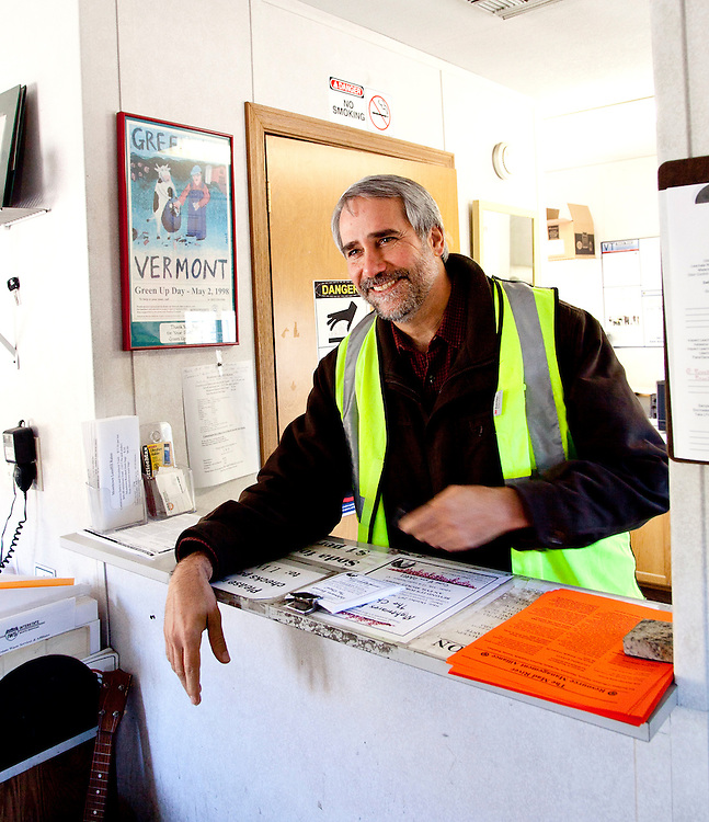 Man wearing yellow reflective safety vest at truck sign-in counter of Landfill office