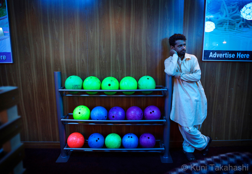 A man leans on bowl rack at bowling alley, The Strikers, in Kabul, Afghanistan on May 6, 2012. The country's first bowling alley was opened in October 2011 by Afghan woman Meena Rahmani to give youths an outlet for entertainment, something that is rare in this war-stricken country. .(Photo by Kuni Takahashi)