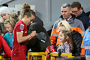 Liverpool women defender Becky Jane (22) signs a young fans  hat during the FA Women's Super League match between Liverpool Women and Everton Women at Anfield, Liverpool, England on 17 November 2019.