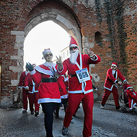 NOALE, ITALY - DECEMBER 18: Participants  dressed as Father Christmas smile as they take part in the Noale Santa Run on December 18, 2011 in Noale, Italy. Close to two thousand people participated in the third annual Noale Santa Run, one of the largest non competitive Santa Run in Italy.