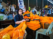 14 JANUARY 2016 - CHACHOENGSAO, CHACHOENGSAO, THAILAND: A woman folds orange cloth wrapped around statues of the Buddha at Wat Sothon. Wat Sothon, in Chachoengsao, is one of the largest Buddhist temples in Thailand. Thousands of people come to the temple every day to pray for good luck, they make merit by donating cooked eggs and cash to the temple. The temple dates from the Ayutthaya period (circa 18th century CE).          PHOTO BY JACK KURTZ