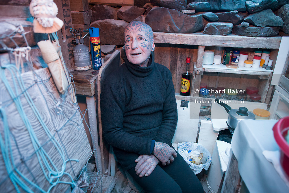 Tattoed hermit Tom Leppard (aka Leopard Man) comfortable in his secret makeshift underground hideaway shelter on Skye, Scotland