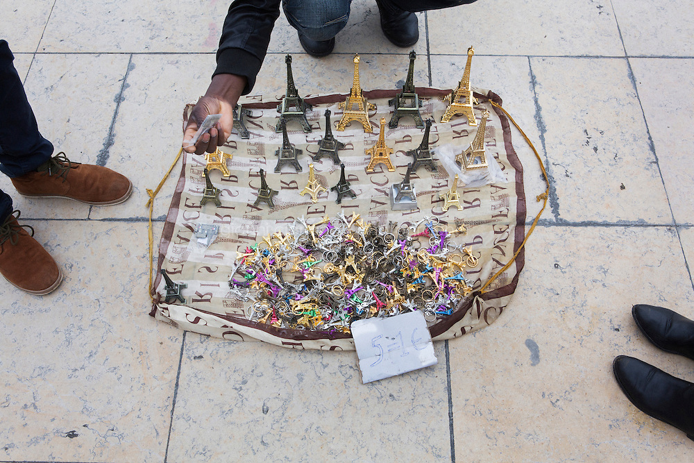 PARIS, FRANCE - 19 NOVEMBER 2014: Miniature Eiffel Towers and keychains sold by African migrants by the Eiffel Tower in Paris, France, on November 19th 2014.<br /> <br /> After crossing the Italian-French border, migrants take the train to Paris. Some stop in Paris, but the majority continues the journey to Calais (before arriving in London), while others go to countries such Germany, the Netherlands, and Sweden.