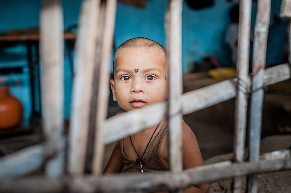 While walking the charming streets of #Hampi in #India I came across this cute #kid looking at me through the wooden sticks that made a sort of window #streetphotography #portrait