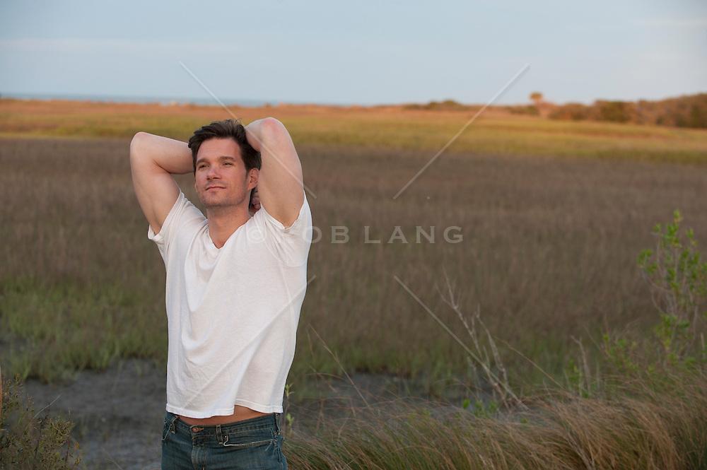 man with his arms behind his head enjoying the marshlands of Charleston, South Carolina