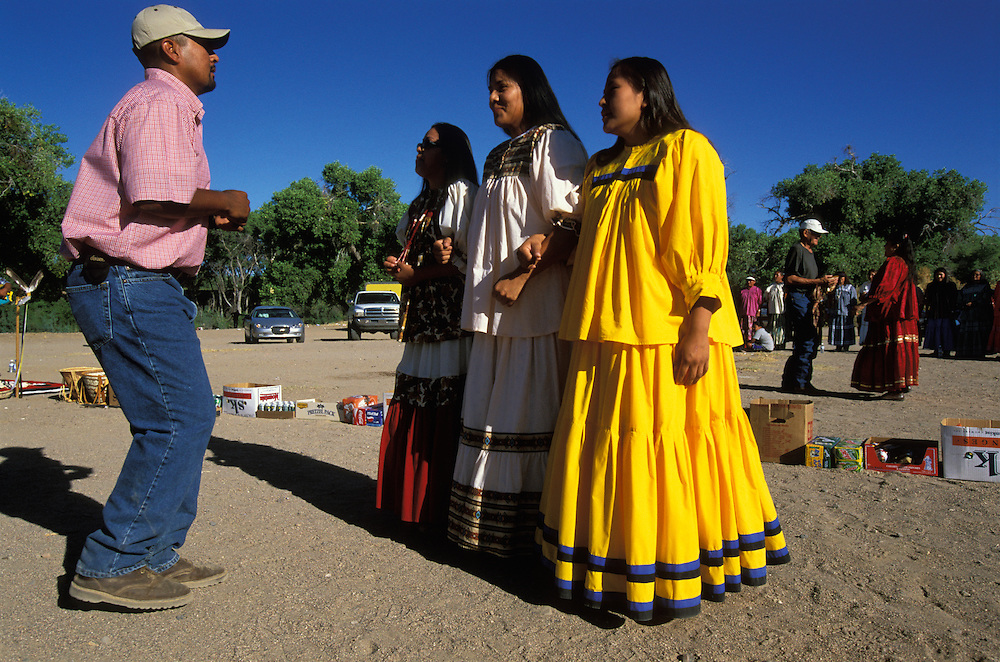 Apache Indians dance at a Sunrise Dance, the first menstruation ceremony of an Apache girl, the San Carlos Indian Reservation, Arizona, USA. The women are dressed in camp dresses.