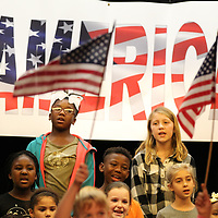 Jniyna Williams, left, and Ava Davenport sing pataraitic songs as they practice their veterans day program with the rest of the third grade class at Lawhon Elementary School iin Tupelo.