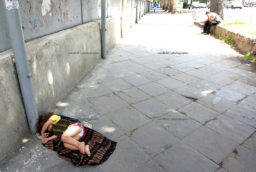A young child sleeps alone on the rustaveli boulevard downtown Tbilisi, while her mother is begging at an other place.