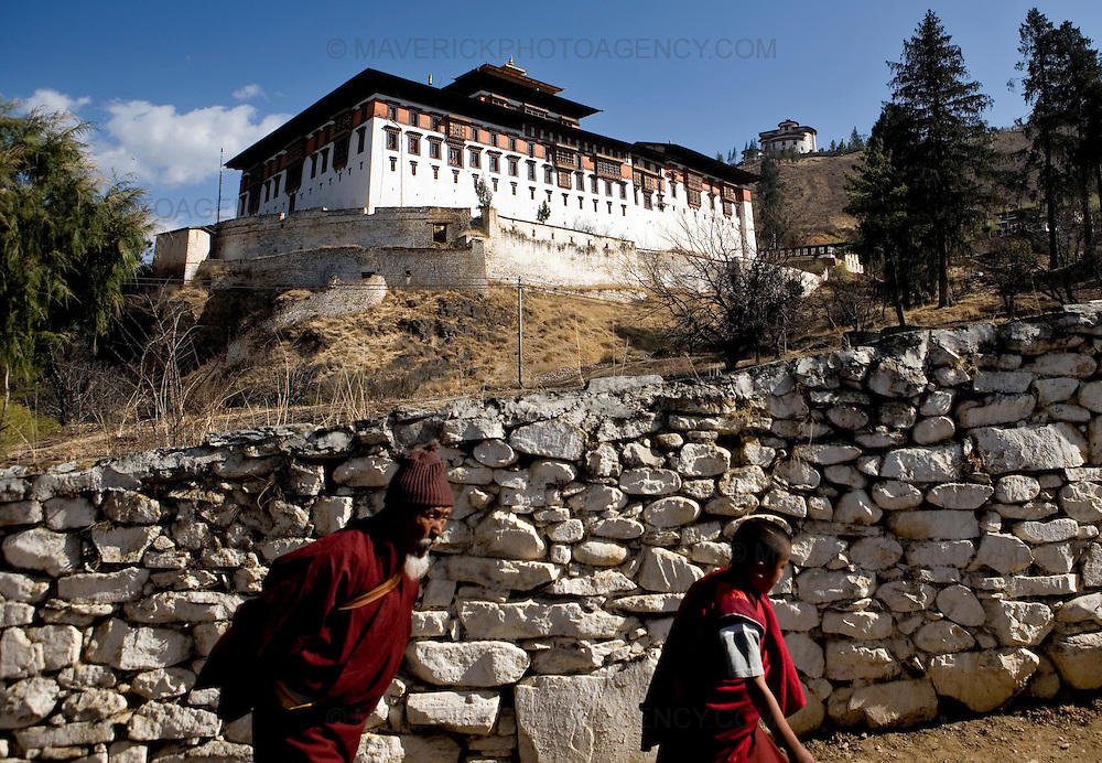 Monk walk to Rinpung Dzong (building pictured) for festival, Paro.Commonly described as the last Himalayan Shangrila, Bhutan is a country of unique serenity, harmony, and beauty. Nestled between India, China, and Tibet, this independent country whose name translates as 'the Land of the Thunder Dragon' has for the past 300 years  proactively followed a policy of isolation and cultural protection. Travel in and out of the country is strictly regulated, and the impact of outside influences on the local culture is carefully monitored. Spirituality is an important aspect of Bhutanese culture, with Buddhism being interlinked with everyday life. Gross National Happiness (GNH), as opposed to GNP/GDP, forms the cornerstone of its development strategy which focuses on a holistic development strategy that complements its cultural and Buddhist spiritual values.