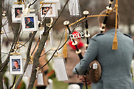 Sean Gearhart plays the bagpipes next to a tree filled with photos of fallen soldiers hang on a tree during National Wreaths Across America Day at Arlington National Cemetery in Arlington, V.A. December 14, 2013.  Among the friends and family members, volunteers also placed thousands of remembrance wreaths on headstones around the cemetery during National Wreaths Across America Day. Photo Ken Cedeno