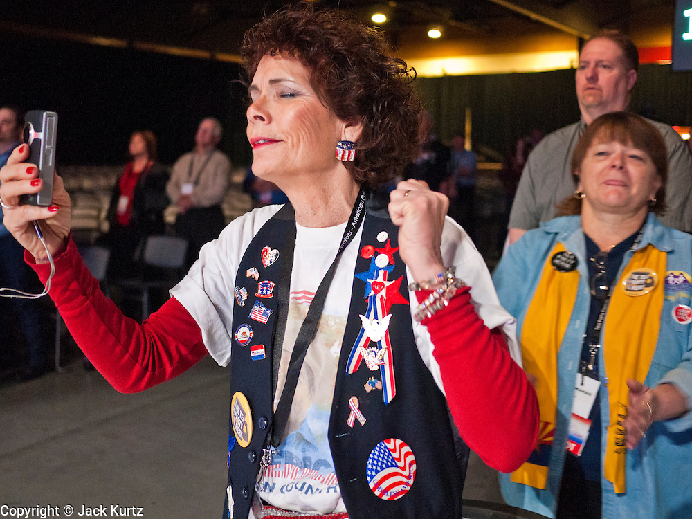 27 FEBRUARY 2011 - PHOENIX, AZ: Members of the Tea Party Patriots stand in prayer during a prayer meeting at the Tea Party Patriots American Policy Summit in Phoenix Sunday, the last day of the conference. About 2,000 people were expected to attend the event, which organizers said was meant to unite Tea Party groups across the country. Speakers included former Minnesota Governor Tim Pawlenty, Texas Congressman Ron Paul, former Clinton advisor Dick Morris and conservative blogger Andrew Brietbart. The event ended with a presidential straw poll, which was won by Herman Cain, a newspaper columnist from Atlanta, GA.     Photo by Jack Kurtz