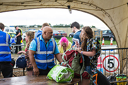 Security checking bags at the Brownstock Festival in Essex.
