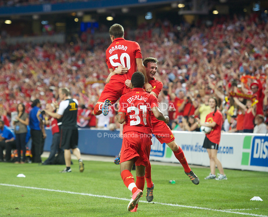 TORONTO, CANADA - Saturday, July 21, 2012: Liverpool's Adam Morgan celebrates scoring the equalising goal against Toronto with team-mates Jack Robinson and Raheem Sterling during the first match of the North American pre-season tour at the Rogers Centre. (Pic by David Rawcliffe/Propaganda)