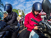 22 JANUARY 2019 - PHRA PRADAENG, SAMUT PRAKAN, THAILAND:  Passengers on  motrbikes check their smart phones on a motorcycle and vehicle ferry crossing the Chao Phraya River in Phra Pradaeng. The use of vehicle ferries across the river has gone down as the government has built bridges to connect communities on both sides of the river. The Phra Pradaeng ferries are the busiest vehicle ferries in the Bangkok metropolitan area. Since the BTS Skytrain now comes close to the ferry, the number of commuters going into Bangkok that use the ferry has increased.    PHOTO BY JACK KURTZ