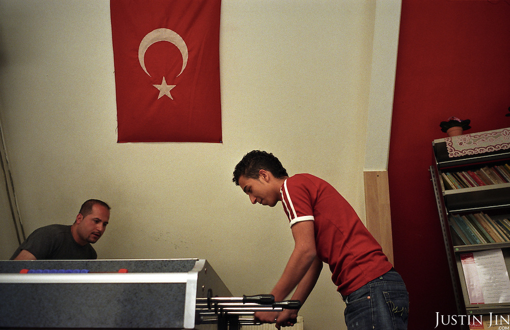 Dutch-Turkish teenager Hakan Dinc plays table football in front of a Turkish flag at a mosque in Amsterdam. .Dinc, 16, was born in the Netherlands. His grandparents from his father?s side came from Turkey in 1971, and his mother came in 1987. Dinc feels more Turkish than Dutch, most of his friends are Turkish and he wants to marry a Turkish girl. During his time off he works in his uncle?s grocery store. Later, he wants to have his own shop. Dinc is following a Commerce course at a vocational school in Amsterdam. .Dinc likes music, pool and chilling out. He has a fourteen-year-old sister and a brother aged ten months. .Picture shot in Amsterdam in 2004 by Justin Jin. .