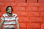 An Italy fan with a painted face sits alone
